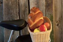 korg med cykeln med äpplen och en rulle Arkivfoto