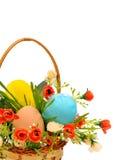 Korg med easter ägg, ro, blommor och grönt gräs Arkivfoton