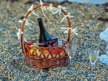 Korg med frukter, flaskan av mousserande vin och mörka exponeringsglas på stranden Två crystal exponeringsglas nära det på kisels Arkivbild