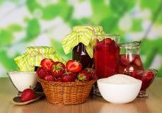 Korg med jordgubbar, driftstopp, dryck, kräm, socker på abstrakt begreppgräsplan Arkivfoton