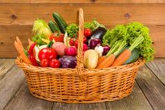 Korg med olika nya grönsaker Arkivfoto