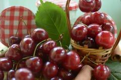 Korg med röda körsbär med stammar och kruset med körsbär på gul bordduk Royaltyfri Fotografi