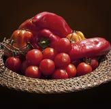 Korg med röda spanska peppar och körsbärsröda tomater royaltyfria bilder