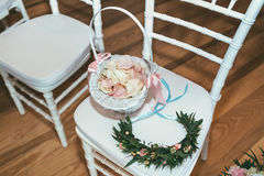 Korg med rosa kronblad på vit stol på bröllopceremoni Royaltyfri Foto