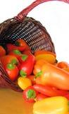 Korg mycket av färgrika peppar som ut spiller på en bordlägga Arkivbild