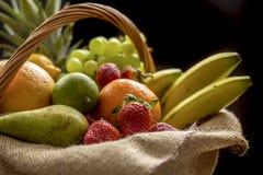 Korg mycket av frukt på en mörk bakgrund arkivbild