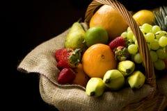 Korg mycket av frukt på en mörk bakgrund arkivfoton