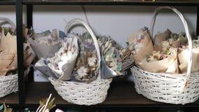 Korgar med buketter av blommor i blomsterhandeln är klart till salu lager videofilmer