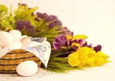 Korgen med påskägg och fjädrar blommor Arkivfoto