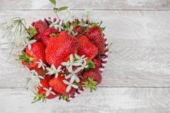 Korghjärta formade med nya jordgubbar och vita blommor som en gåva för dag för valentin` s kopiera avstånd Arkivbilder
