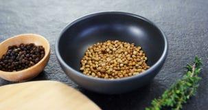 Korianderzaden, zwarte peper, rozemarijnkruiden en houten raad stock videobeelden