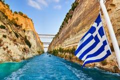 Korinth-Kanal in Griechenland und griechische Markierungsfahne auf Lieferung stockfotografie