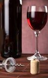Kork och korkskruv med flask- och vinexponeringsglas Fotografering för Bildbyråer