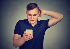 Korkad dum grabb som har problem med hans smarta telefon royaltyfri fotografi
