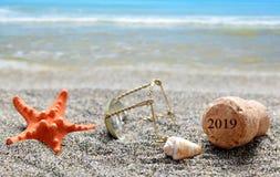 Korkpropp av champagne med numret 2019 och snäckskalet med sjöstjärnan på sandstranden royaltyfria bilder
