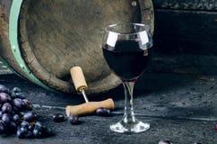 Korkskruv bredvid en trävinfat Vin på en trätrumma Bränd svart träbakgrund Tappning Copyspace för en text Gr Royaltyfri Fotografi
