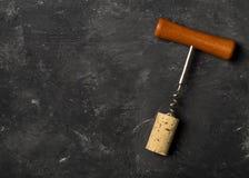 Korkskruv med vinkork på det mörka träbrädet, lekmanna- bästa sikt för lägenhet Arkivfoto