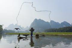 Kormoran, Fischmann und Li River-Landschaftsanblick mit Nebel im sprin Stockbild