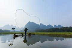 Kormoran, Fischmann und Li River-Landschaftsanblick mit Nebel im sprin Stockfotografie