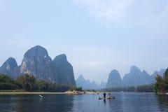 Kormoran, Fischmann und Li River-Landschaftsanblick mit Nebel im sprin Lizenzfreie Stockfotos