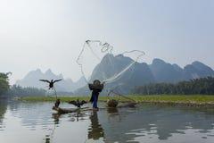 Kormoran, Fischmann und Li River-Landschaftsanblick mit Nebel im sprin Stockfoto