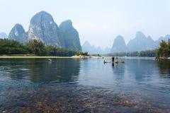 Kormoran, Fischmann und Li River-Landschaftsanblick mit Nebel im sprin Stockfotos