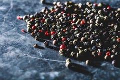 Korn av blandad peppar som spills på räknare Royaltyfri Bild