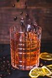 Korn av kaffe faller in i ett exponeringsglas med en drink Arkivfoto