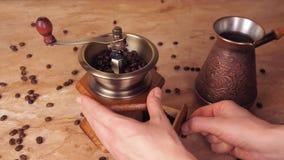 Korn av kaffe hälls in i en kaffekvarn Från behållaren för att lagra kaffe, häller tagandekaffekorn och in i en hand arkivfilmer
