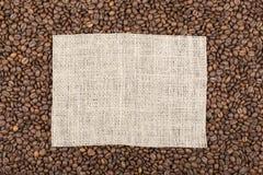 Korn av kaffe i som i mitten en rektangel av säckvävwi arkivbilder