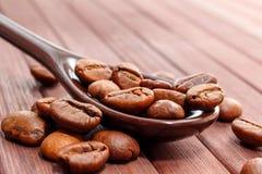 Korn av kaffenärbilden Kaffebönor lokaliseras på en sked a royaltyfri fotografi
