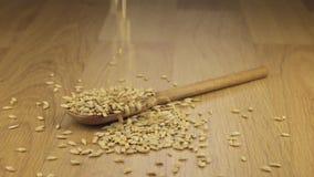 Korn av korn som faller på träskeden som ligger på en träyttersida stock video
