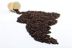 Korn av svart kaffe i form av fastlandet på en vit bakgrund royaltyfria bilder