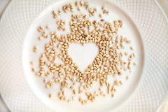 Korn för pärlemorfärg korn i en form av hjärta spillde på en platta fotografering för bildbyråer