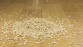Korn för pärlemorfärg korn som faller på en hög av pärlemorfärg korn arkivfilmer