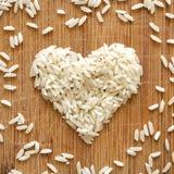 Korn för vita ris i hjärta formar på träskärbräda, i det fyrkantiga formatet för socialt massmedia, baner och bakgrunder Royaltyfri Foto