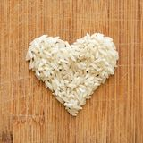 Korn för vita ris i hjärta formar på träskärbräda, i det fyrkantiga formatet för socialt massmedia, baner och bakgrunder Arkivbilder