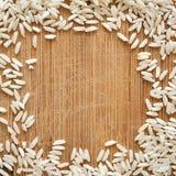 Korn för vita ris på träskärbräda, i det fyrkantiga formatet för socialt massmedia, baner och bakgrunder Royaltyfri Fotografi