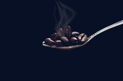 Korn grillade kaffeskeden med rök på mörk bakgrund med skuggning Arkivfoto