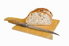 Kornbröd klippte på en träskärbräda med en brödkniv på en vit bakgrund arkivfoto
