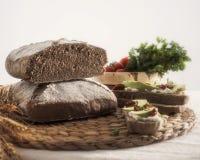 Kornbröd med avokadot på rostat bröd, gräddost och torkade tomater Royaltyfri Bild