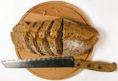 Kornbrot mit Messer Stockbild