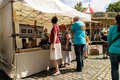 KORNELIMUENSTER,德国, 2017年6月18日, -人们在一晴朗的温暖的天浏览Kornelimuenster历史的市场  图库摄影