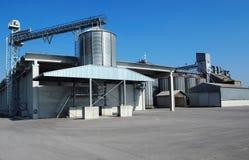 Kornlagringsfack med silor och fördelningssystemet Asfaltfyrkanten av den är framme tom Arkivfoton