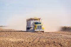 Kornlastbilkorsningen kantjusterade fältet med slingan av damm Arkivbilder