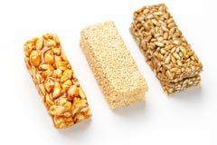 Kornmüsliriegel mit Erdnüssen, indischem Sesam und Samen in Folge auf einem weißen Hintergrund Sortierte Stangen der Draufsicht d stockfotografie