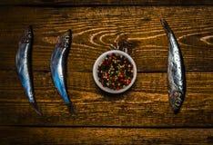 Kornpeppar och fisk på tabellen Arkivfoto