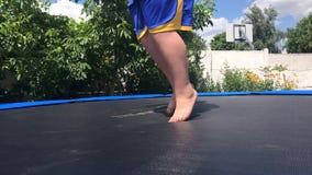 KOROSTEN - JULE, 4, 2019: nogi chłopiec skacze na trampoline w plenerowym w skrótach zbiory