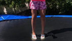 KOROSTEN - JULE, 4, 2019: piernas de la niña en los pantalones cortos que saltan en el trampolín en al aire libre almacen de metraje de vídeo