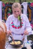 Korosten, Ucrânia - 6 de setembro de 2016: abra o óleo de derramamento da jovem mulher da cozinha em fritar panquecas de batata Fotos de Stock Royalty Free
